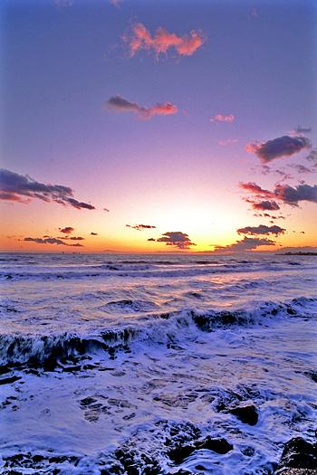 Sunset over foamy ocean waves