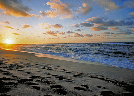 Far sunset over a seashore with breaking waves