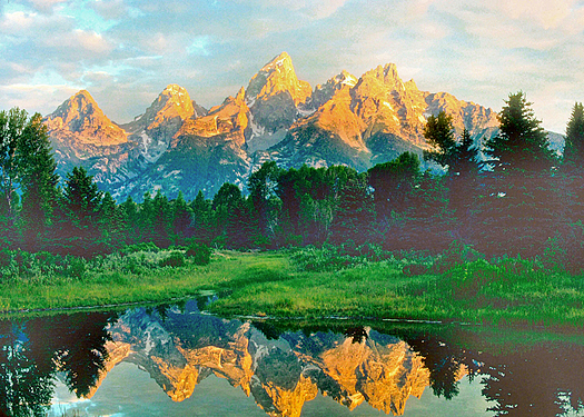 Sun-tipped mountains reflected in foreground lake