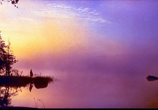 Single figure viewing sunset over misty purple lake