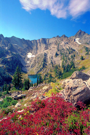 Isolated mountain lake amid rocky peaks with foreground of red flowers