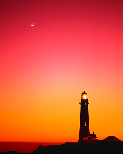 Lighthouse at sunset with moon overhaed