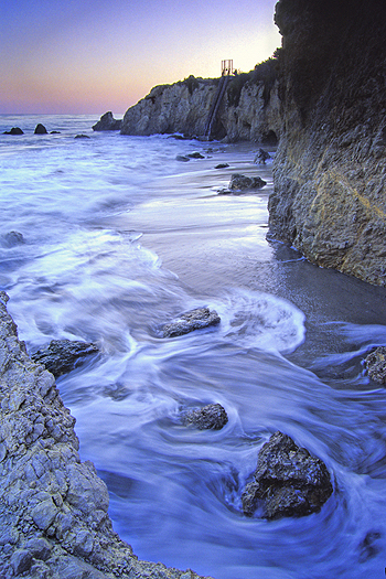 Swirling tidal waters beneath rocky cliffs at seashore