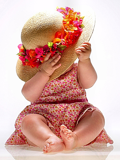 Seated baby in pink-flowered dress with straw hat over her face