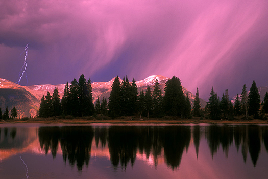 A reflecting mountain lake with a pink and purple sky after a storm