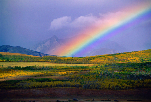 Large rainbow over Fall-colored mountain