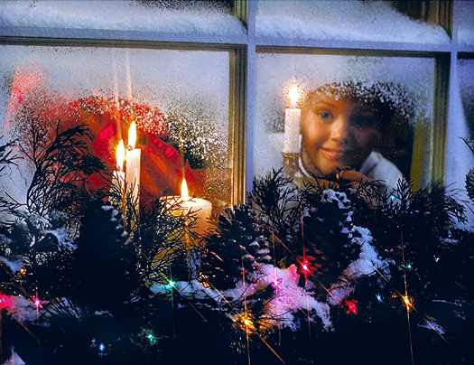 A child's expectant face seen through a frosted window with Christmas candles