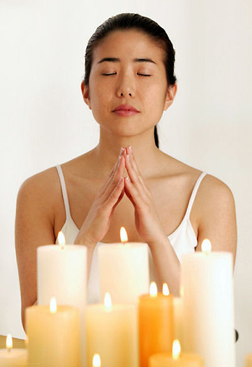 Praying young woman with candles
