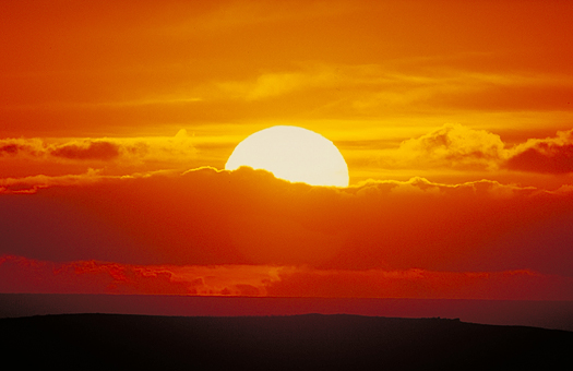 Large golden setting sun behind red clouds