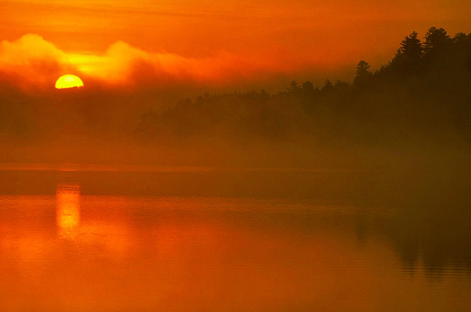 Yellow sun setting in red and cloudy sky over red lake