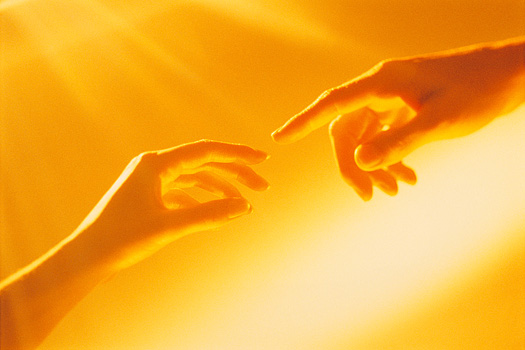 Two hands almost touching each other in a golden glow