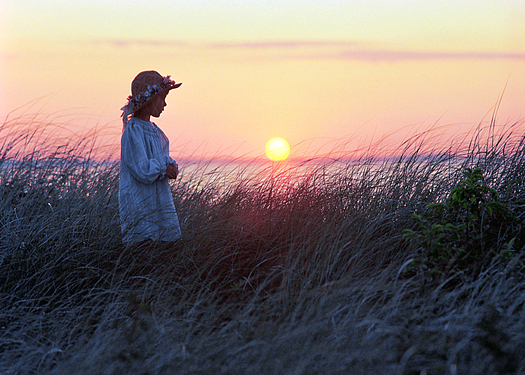 A young girl in a sunhat walking through grass with sunset over the ocean as a backdrop