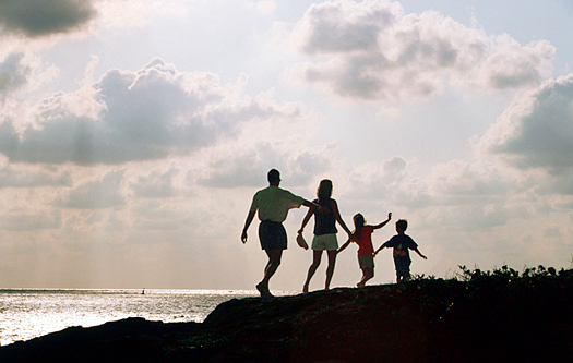 Family of four in silhouette walking on a beach
