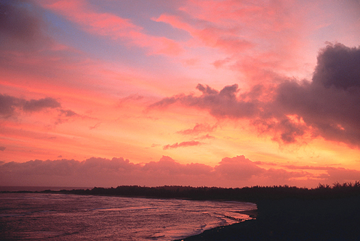 red and pink sunset over a seashore