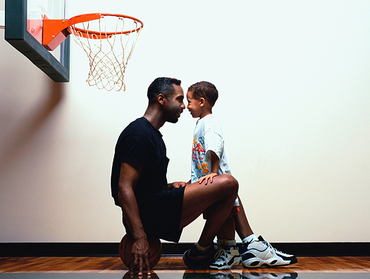 Father and young son on basketball court