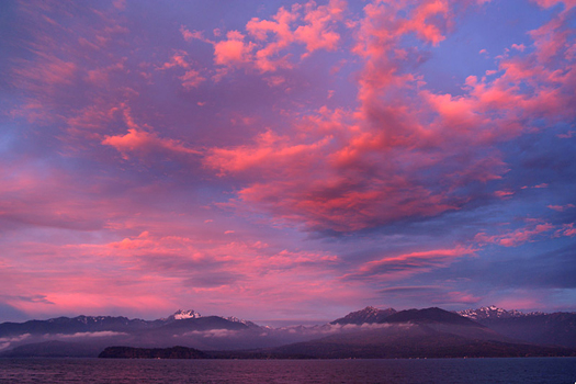 Pink and red clouds at sunset on a blue sky by Don Paulson