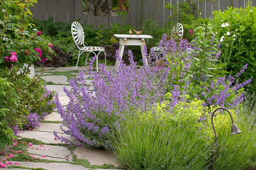 Table and chairs in a flower garden by Don Paulson