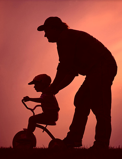 Silhouette of father teaching child to ride bike