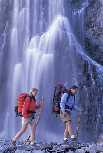 Couple hiking by a cascading waterfall