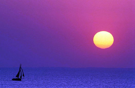 Lone Sailboat on the ocean with the Setting Sun