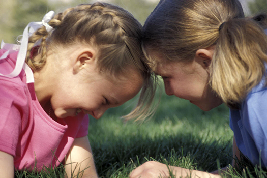 Two little girls with their heads together playing together outside
