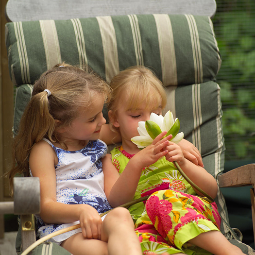 Two girls in a chair looking at a flower