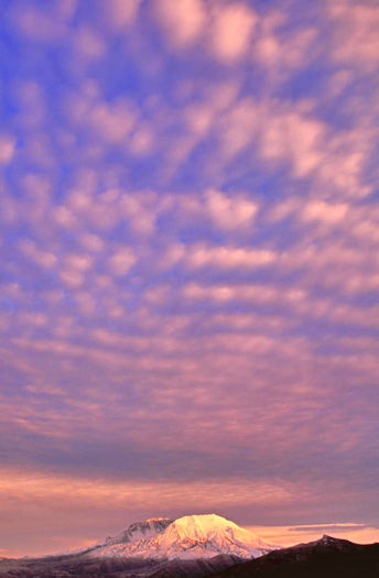 Mountain sky with interesting cloud formations in pink and blue