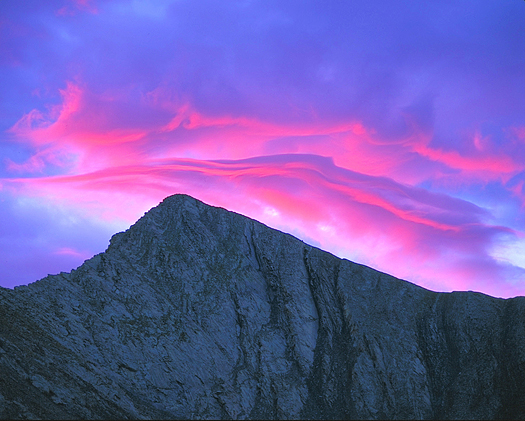 Blue mountaintop against pink sunset clouds by John Fielder