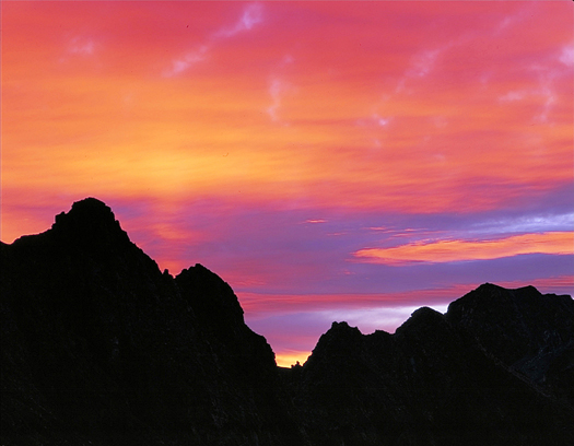 Silhouetted mountain landscape against pink-orange sunset by John Fielder