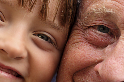 A young child and an old man in closeup