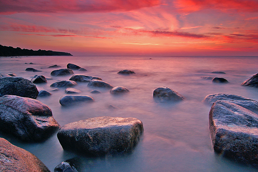 Coastal sunset with foreground rocks and red sky