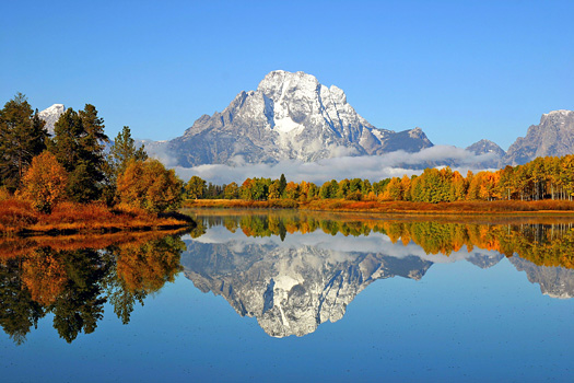 Snow-capped mountain peak reflected in a still blue pond