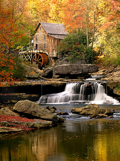 Fall scene at a mill with a water wheel and a small waterfall in the foreground