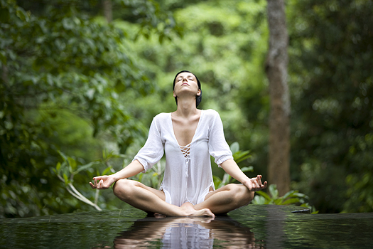 Woman in yoga pose in a pool of water in the forest