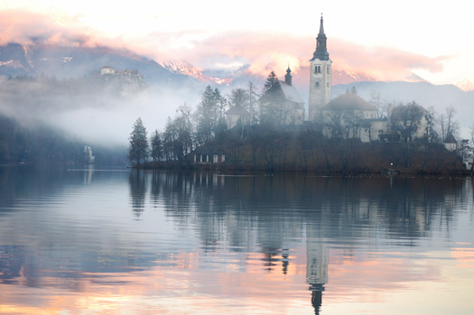 The Bled island church reflecting in the water with the snowy mountains and the Bled castle in the background