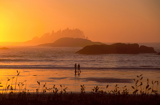 Two people walking on a beach during a sunset in Tofino, British Columbia.
