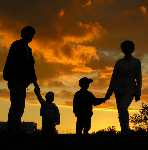 family of four silhouetted against a sunset sky