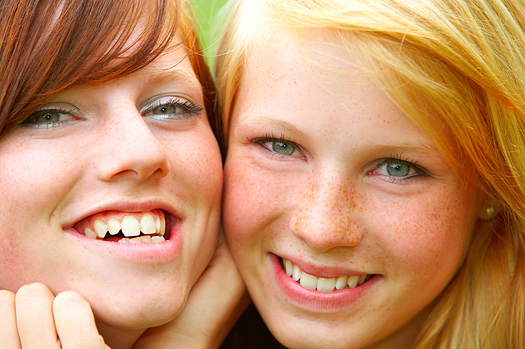 Two smiling young teen girls. Close-up.
