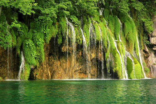 Waterfall over mossy stones and green pool