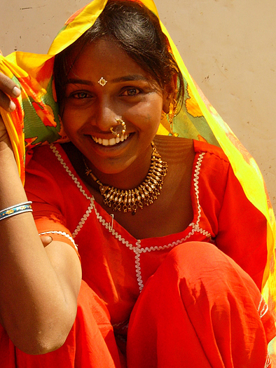 a smiling young village girl in india in a red sari and yellow scarf