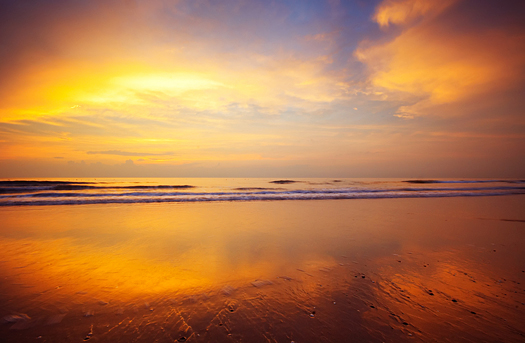 Sunset and ocean background in yellow and gold
