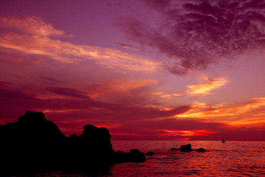 A dramatic ocean sunset in red and purple