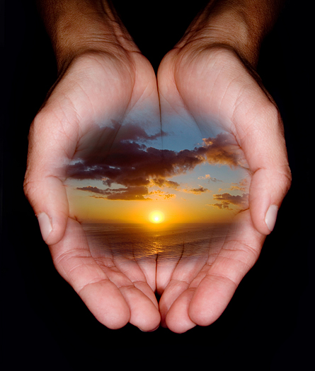 female hands holding image of beautiful sunset over the ocean