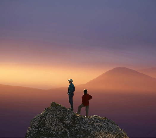 Man and woman overview sunset landscape from rocky peak