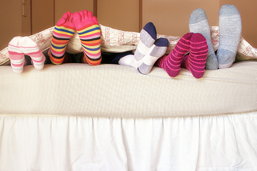 Family Bed: Five pairs of feet in colorful socks peek from under the covers