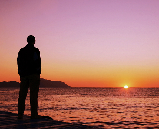 Man silhouetted at sunset on sea pier