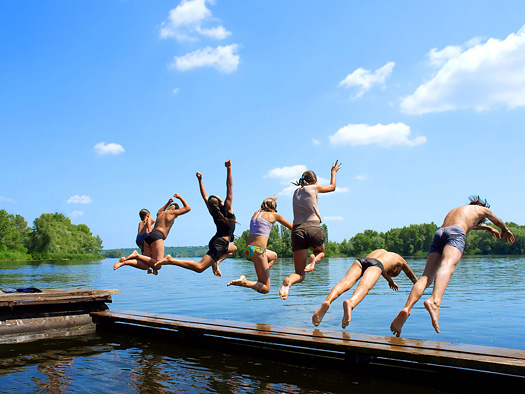 group of kids jumps into water from pier. Shot in June, Dnieper river, Ukraine.