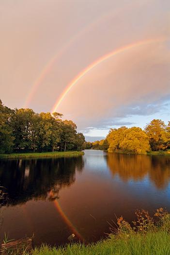double reflected rainbow over autumn pond