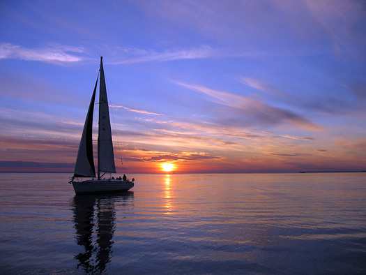 Single sailboat silhouetted against sunset