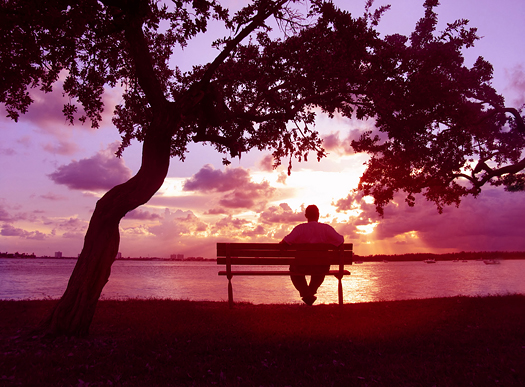 Man sitting on a bench enjoying sunset on the lake